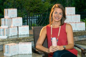 Wellness | Amy Kuchar, co-founder of Rosé Water, smiling with a Rosé Water can in her hand.
